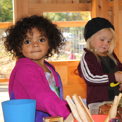Two young children interacting at activity table